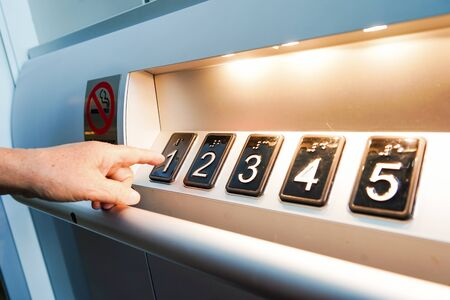 Press elevator or lift numeric button control panel at hotel.