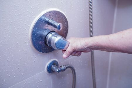 Asian senior or elderly old lady woman patient use toilet bathroom to open shower in nursing hospital ward, healthy strong medical concept.