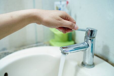 Asian middle-aged lady woman patient open the faucet to washing hands in the hospital ward : healthy medical concept.