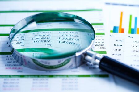 Magnifying glass on charts graphs spreadsheet paper. Financial development, Banking Account, Statistics, Investment Analytic research data economy, Stock exchange trading, Business office company meeting concept. Stockfoto