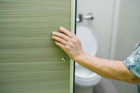 Asian senior elderly old lady woman patient open toilet bathroom by hand in nursing hospital ward, healthy strong medical concept. Foto de archivo - 129624754
