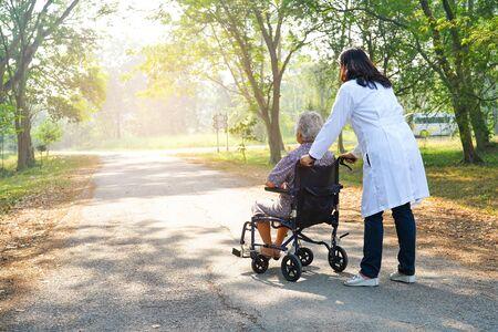Médico ayuda y cuidado Paciente asiático mayor o anciano mujer sentada en silla de ruedas en la sala del hospital de enfermería: concepto médico fuerte y saludable