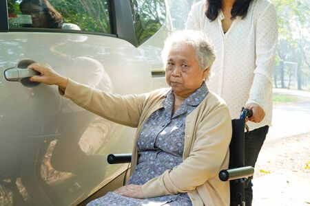 Asian senior or elderly old lady woman patient sitting on wheelchair prepare get to her car : healthy strong medical concept. Stock Photo