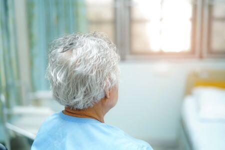 Asiatische ältere oder ältere alte Dame, die mit Hoffnung auf dem Bett in der Krankenstation sitzt und auf ihren Verwandten wartet: gesundes, starkes medizinisches Konzept. Standard-Bild