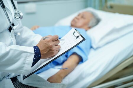 Lekarz zapisuje diagnozę w schowku, podczas gdy azjatycki starszy lub starsza starsza kobieta leżąca na łóżku na oddziale szpitala pielęgniarskiego: zdrowe silne pojęcie medyczne.