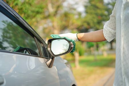 Cleaning car with green color microfiber cloth outdoor in holiday. Foto de archivo