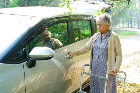 Asian senior or elderly old lady woman patient sitting on wheelchair prepare get to her car : healthy strong medical concept.