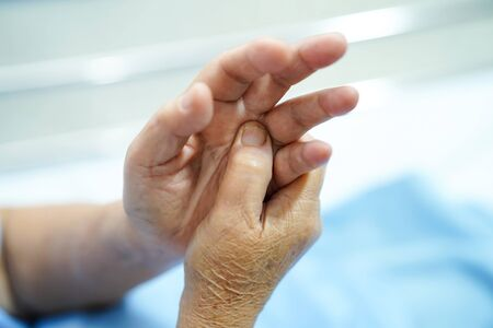 Asian senior or elderly old lady woman patient feel pain her hand on bed in nursing hospital ward : healthy strong medical concept.