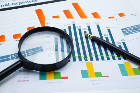 Szkło powiększające na wykresach wykresy w arkuszu kalkulacyjnym. Rozwój finansowy, konto bankowe, statystyka, gospodarka danymi analitycznymi inwestycyjnymi, handel na giełdzie, koncepcja spotkania biznesowego biura firmy.