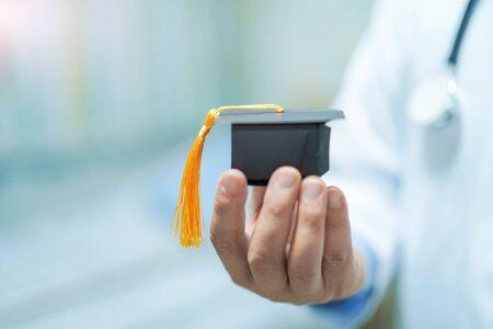 Asiatisches Doktorstudium lernen mit Abschlusslückenhut in der Krankenstation: kluges helles geniales Bildungsmedizinkonzept. Standard-Bild