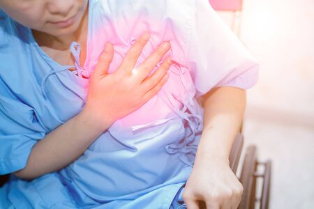 Asian middle-aged lady woman patient chest pain may be a symptom of a heart attack in the hospital ward : healthy medical concept Stock Photo - 130343727