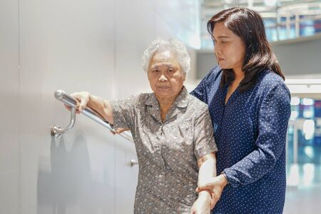 Asian senior or elderly old lady woman patient use slope walkway handle security with help support assistant in nursing hospital ward : healthy strong medical concept.