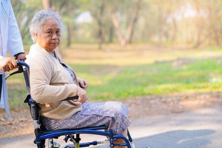 Doctor help and care Asian senior or elderly old lady woman patient sitting on wheelchair at nursing hospital ward : healthy strong medical concept Stock Photo