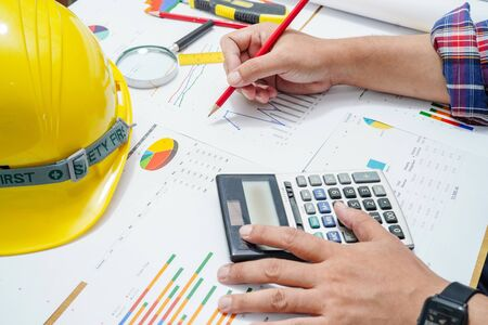 Architect or engineer working project accounting with graph with tools in office, Construction account concept.