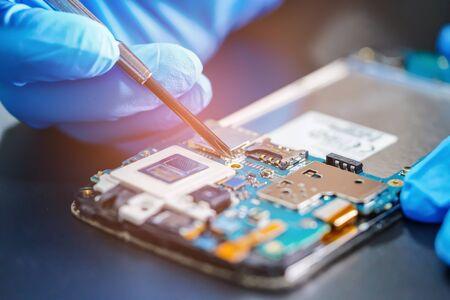 Aziatische technicus die microcircuit-hoofdbord van elektronische smartphonetechnologie repareert: computer, hardware, mobiele telefoon, upgrade, schoonmaakconcept. Stockfoto
