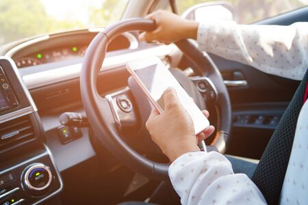 Holding mobile phone in car to communication with family and friends. Imagens