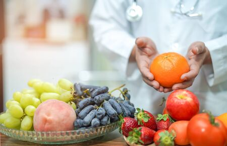 Nutritionist doctor holding orange juice with strawberry, potatoes, apples, plum, grapes, carrot, peach, pumpkin and salad vegetable on desk to instruction healthy food strong patient.