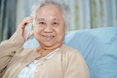 Asian senior or elderly old lady woman patient with credit card talking on the mobile phone while sitting and happy on bed in nursing hospital ward : healthy strong medical concept Banco de Imagens