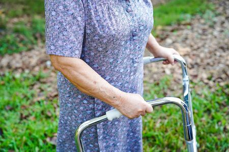 Asian senior or elderly old lady woman patient walk with walker in park, healthy strong medical concept Stok Fotoğraf