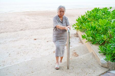 Asian senior or elderly old lady woman patient use slope walkway handle security with help support assistant at sea in holiday : healthy strong medical concept.