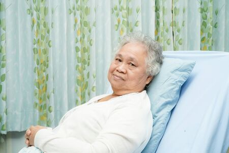 Asian senior or elderly old lady woman patient smile bright face while sitting on bed in nursing hospital ward : healthy strong medical concept