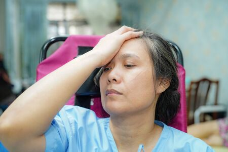Asian middle-aged lady woman patient worry about sickness, headache and feel sad in the hospital ward : healthy medical concept Banco de Imagens