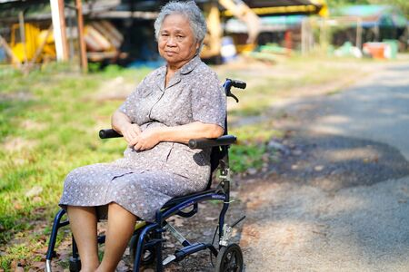 Asian senior or elderly old lady woman patient on wheelchair in park : healthy strong medical concept Banco de Imagens
