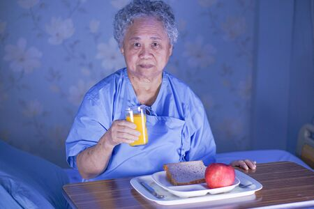 Asian senior or elderly old lady woman patient eating breakfast healthy food with hope and happy while sitting and hungry on bed in hospital. Banco de Imagens