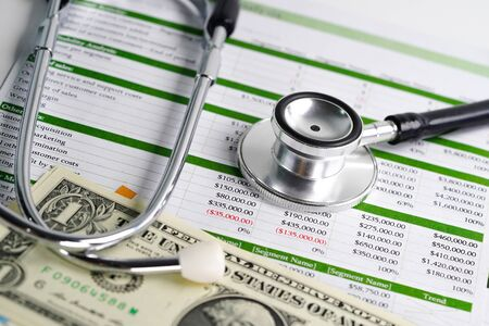 Stethoscope and US dollar banknotes on spreadsheet paper, Financial, account, statistics and business data medical health concept.