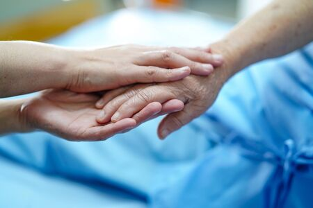 Holding Touching hands Asian senior or elderly old lady woman patient with love, care, helping, encourage and empathy at nursing hospital ward : healthy strong medical concept Banco de Imagens