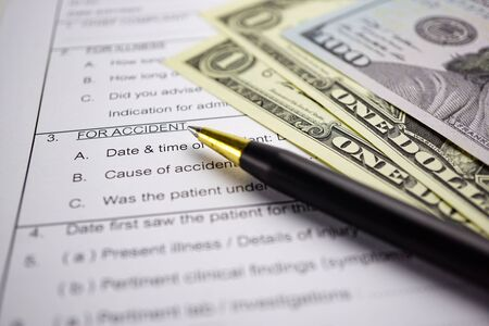 Health insurance accident claim form with stethoscope and US dollar banknotes, Medical concept.