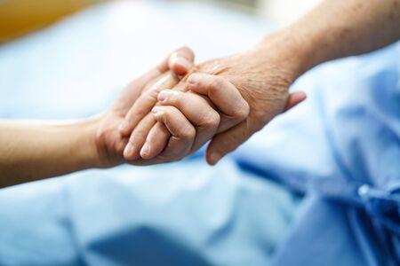 Händchen haltend asiatische Senioren oder ältere alte Frauenpatientinnen mit Liebe, Fürsorge, Hilfe, Ermutigung und Empathie auf der Krankenstation: gesundes, starkes medizinisches Konzept