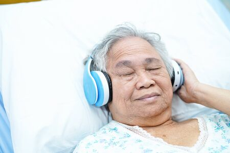 Asian senior or elderly old lady woman patient use earphone while lie down and happy on bed in nursing hospital ward : healthy strong medical concept