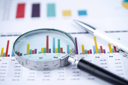 Magnifying glass on charts graphs spreadsheet paper. Financial development, Banking Account, Statistics, Investment Analytic research data economy, Stock exchange trading, Business office company meeting concept. Banco de Imagens