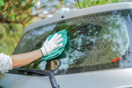 Cleaning dust dirty back window glass car with green microfiber cloth in holiday. Stock Photo