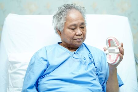 Asian senior or elderly old woman patient holding to use denture on the bed in nursing hospital ward : healthy strong medical concept