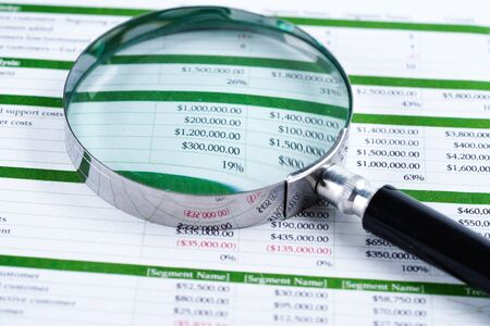 Magnifying glass on spreadsheet paper. Financial development, Banking Account, Statistics, Investment Analytic research data economy, Stock exchange trading, Business office company meeting concept.