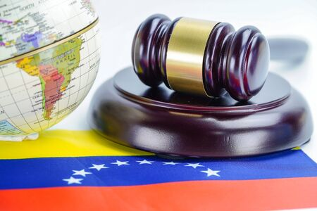 Venezuela flag and Judge hammer with globe world map. Law and justice court concept.