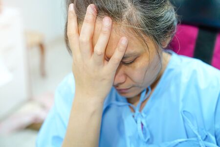 Asian middle-aged lady woman patient worry about sickness, headache and feel sad in the hospital ward : healthy medical concept