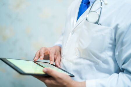 Asian smart man doctor holding digital tablet technology to search knowledge solve treatment for patient in nursing hospital ward : healthy strong medical concept.