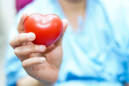 Asian middle-aged lady woman patient holding red heart in her hand with bright face on wheelchair in nursing hospital ward : healthy strong medical concept