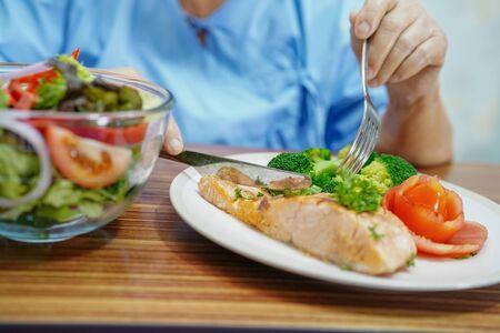 Asiatische ältere oder ältere alte Dame Patientin, die gesundes Frühstück mit Hoffnung isst und glücklich ist, während sie im Krankenhaus sitzt und hungrig auf dem Bett sitzt. Standard-Bild