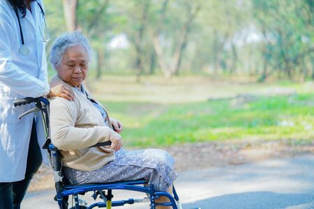 Doctor help and care Asian senior or elderly old lady woman patient sitting on wheelchair at nursing hospital ward : healthy strong medical concept Banco de Imagens