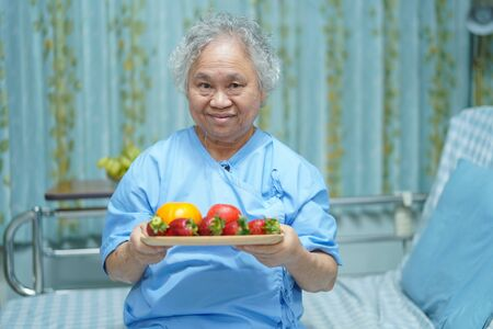 Asian senior or elderly old lady woman patient holding fruits healthy food with hope and happy while sitting and hungry on bed in hospital.