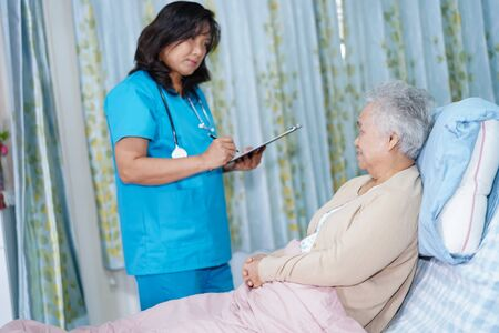 Doctor talking about diagnosis and note on clipboard with Asian senior or elderly old lady woman while lying on bed in nursing hospital ward : healthy strong medical concept. Banco de Imagens