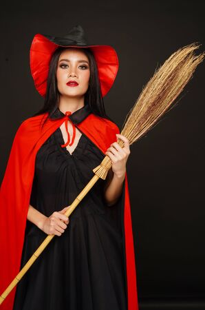 Asian beautiful woman in witches hat and costume with broom in halloween festival. Banco de Imagens