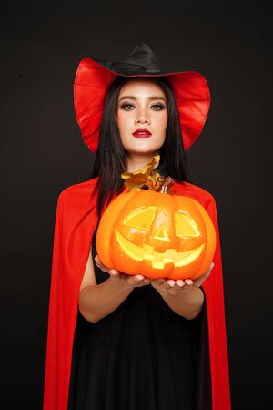 Asian beautiful woman in witches hat and costume holding pumpkin in halloween festival.