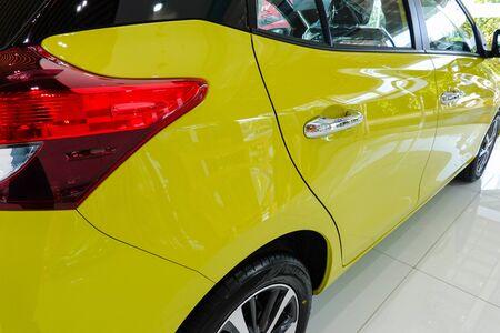 Yellow modern new car in showroom.