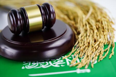 Saudi Arabia flag and Judge hammer with gold grain rice from agriculture farm. Law and justice court concept.