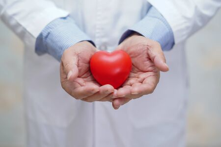 Doctor holding red heart in his hand in nursing hospital ward : healthy strong medical concept  Archivio Fotografico